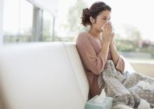 woman sneezing into tissue at home, struggling with poor indoor air quality