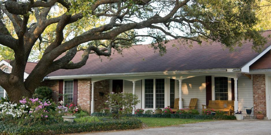 white and brick ranch home with large oak tree in front